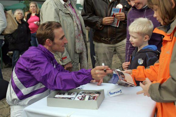Mit Kindern ganz besonders geduldig: Andrasch Starke beim Autogrammeschreiben. www.galoppfoto.de
